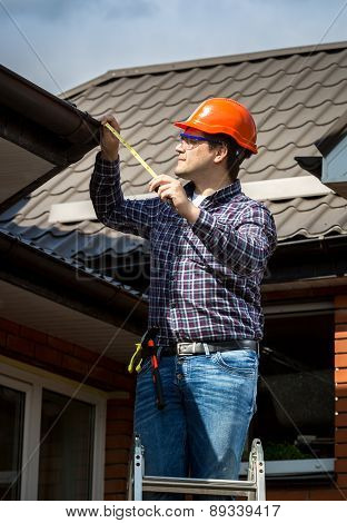 Handyman Standing On High Ladder And Measuring Roof With Tape
