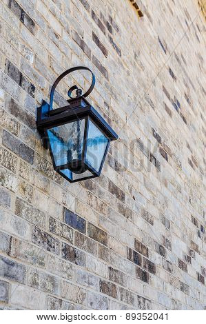 A classic black iron light fixture on a brick wall poster