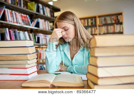 people, knowledge, education, literature and school concept - bored student girl or young woman with books dreaming in library