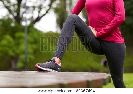 fitness, sport, training, people and lifestyle concept - close up of woman stretching leg and doing lunge on bench in park