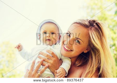 family, child and parenthood concept - happy mother with little baby outdoors