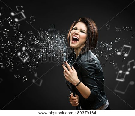 Female rock musician holding sounding mike with melody in the air on grey background
