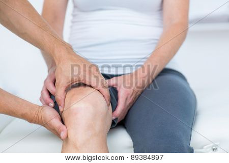 Doctor examining his patients knee in medical office