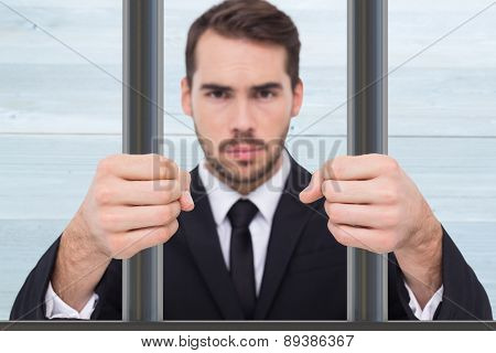 Exasperated businessman with clenched fists against bleached wooden planks background
