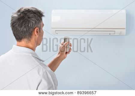 Man Using Air Conditioner Remote