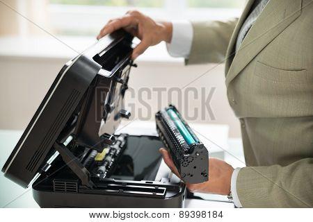 Businessman Fixing Cartridge In Photocopy Machine