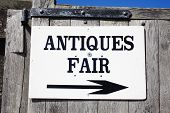 Antique sign directing buyers to an outdoor antiques retail fair poster