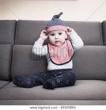Caucasian baby boy weared bib  sitting on sofa at home