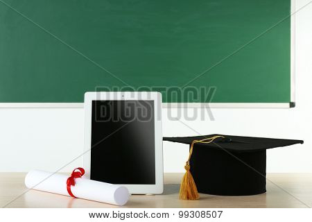 Graduation cap with tablet and diploma on table in class