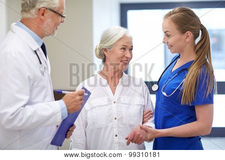 medicine, age, health care and people concept - male doctor with clipboard, young nurse and senior woman patient talking at hospital corridor poster