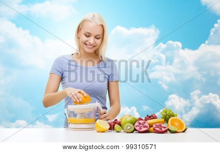 healthy eating, vegetarian food, diet, detox and people concept - smiling woman with squeezer squeezing fruit juice over blue sky and clouds background