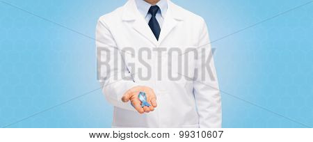 healthcare, profession, people and medicine concept - close up of male doctor in white coat holding sky blue prostate cancer awareness ribbon