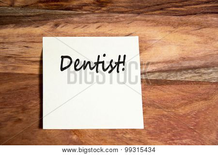 the word dentist writen on a yellow memo