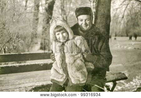 Vintage photo of mother and daughter sitting on bench in winter, 1950's
