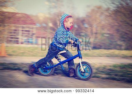 little boy riding runbike