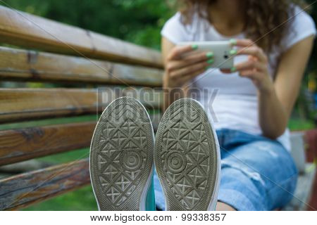 Soles Shoe Closeup. Girl In Jeans Using A Mobile Phone