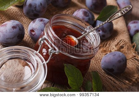 Delicious Plum Jam In A Glass Jar On The Table Close-up. Horizontal
