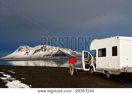 Photographer taking photos of beautiful Icelandic landscape outside mobile motor home RV camper van traveling through Iceland, free and easy holiday