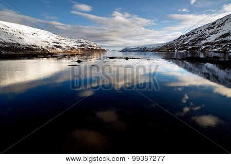 beautiful reflection of clouds in the still water of the fjord, scenic landscape of iceland westfjords