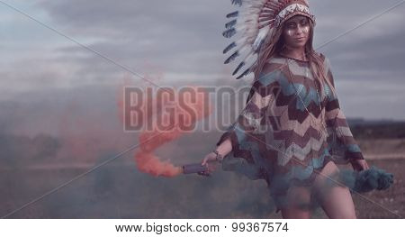 ethnic native american woman with the smoke on the field