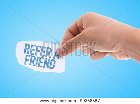 Piece of paper with the word Refer a Friend with blue background