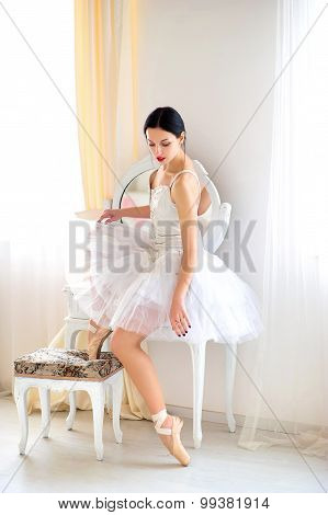 Beauty brunette ballerina in interior, wearing ballet skirt and corset