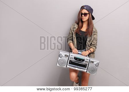 Cool teenage girl in hip hop outfit holding a ghetto blaster and leaning against a gray wall