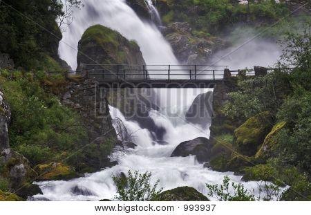 Bridge Across The Stream Near A Powerful Waterfall
