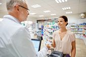 medicine, pharmaceutics, health care and people concept - smiling woman with wallet giving money to senior man pharmacist at drugstore cash register poster