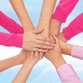 feminism, women power and breast cancer awareness concept - close up of women hands on top of each other over white background poster