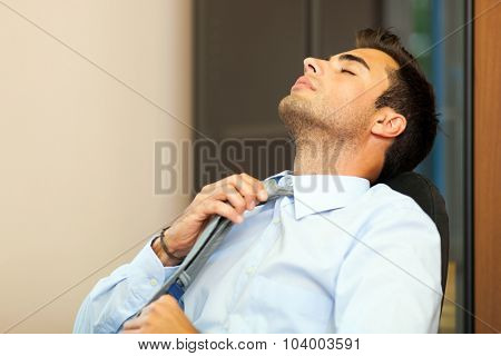 Businessman loosening his collar for relax