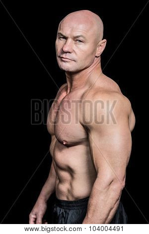 Portrait of shirtless bald man standing against black background