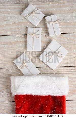 High angle photo of five Christmas presents wrapped in white paper and tied with white string and a stocking. The gifts are on a whitewashed wood table. Vertical with Snow effect.