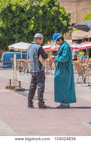 TAROUDANT, MOROCCO, APRIL 9, 2015: Two local men, one in traditional attire, chat outdoor