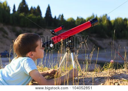 boy at dawn looking through a telescope