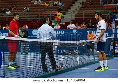 KUALA LUMPUR, MALAYSIA - OCTOBER 01, 2015: Mischa Zverev (red) and Feliciano Lopez waits for the coin toss to start their match at the Malaysian Open 2015 Tennis tournament held at the Putra Stadium.