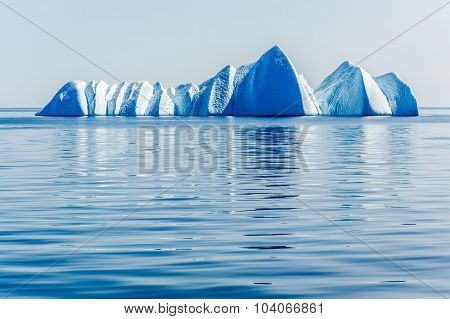 Group of powerful icebregs float silenly in the ice blue Arctic Ocean.
