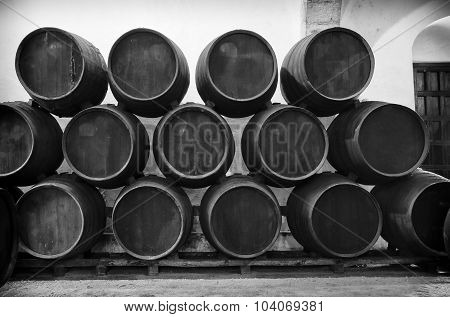 Barrels stacked in the winery in black and white poster