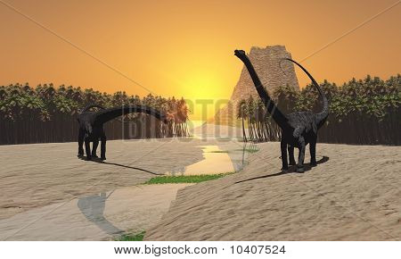 Two Diplodocus dinosaurs come to a river for a drink in prehistoric times. poster