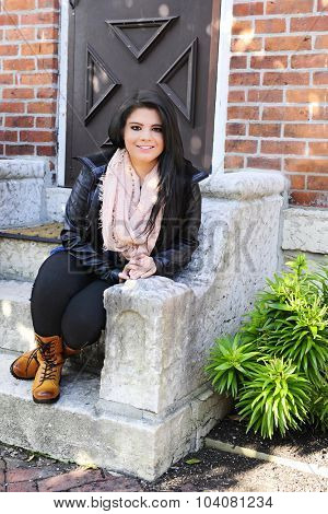 A beautiful teen girl happily sitting on her front stoop in the shade on a sunny day.