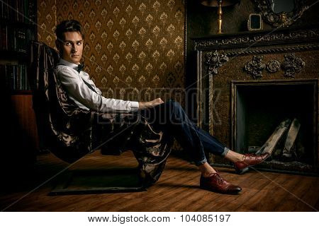 Elegant handsome young man sitting by the fireplace in a room with classic vintage interior. Fashion shot.