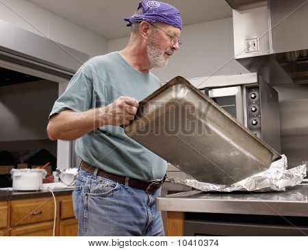 Older Man Cleaning A Pan