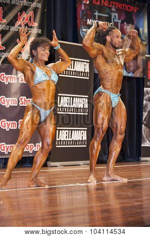Bodybuilding Duo In Front Double Biceps Pose On Stage