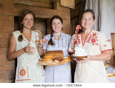 Women with farm-style meal in rural house interior poster