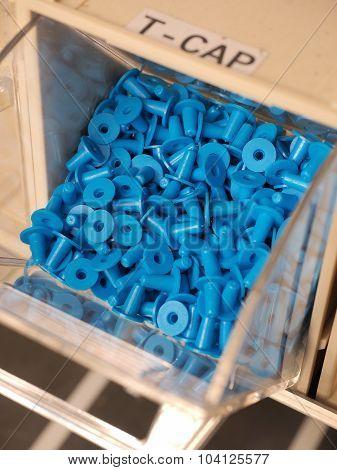 T -shaped plastic plugs in a storage organizer