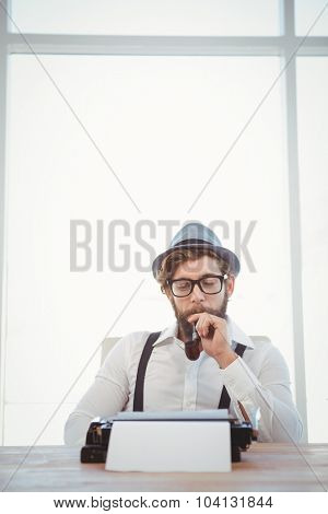 Hipster smoking pipe while sitting looking at typewriter on desk in office
