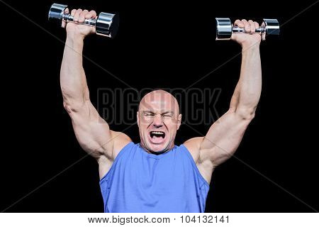 Muscular man with arms raised lifting dumbbells