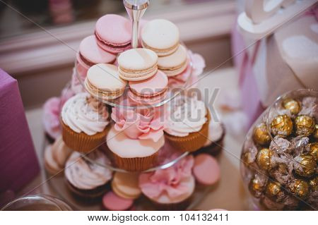 Wedding Decoration With Pastel Colored Cupcakes, Meringues, Muffins And Macarons.