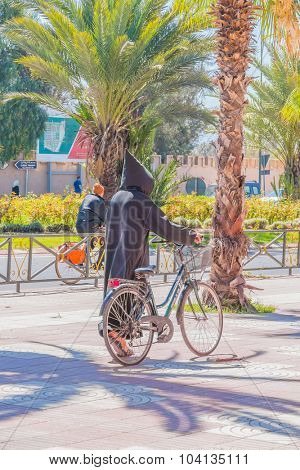 TAROUDANT, MOROCCO, APRIL 9, 2015: Local man in traditional attire walks with his bike