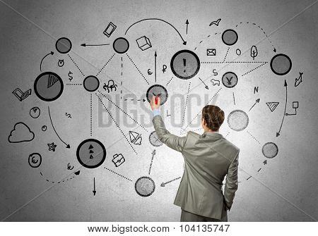 Back view of businessman drawing connection lines on wall